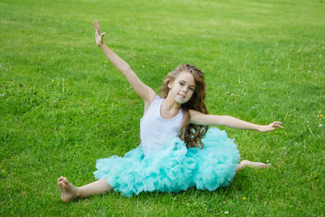 Charming little girl in a smart fluffy tulle skirt sitting on a twine on the green grass in a summer park