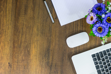 Office desk table Top view with laptop, supplies, notebook, pen, flower and blank white paper on wooden table background. Top view with copy space