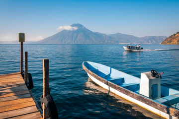 Beautiful View of Volcano San Pedro from the shore of Lake Atitlan in Guatemala with a tourist boat docked at a pier.