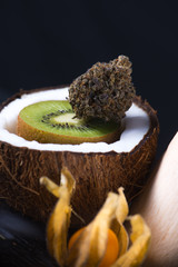 Detail of cannabis buds with fresh coconut and kiwi over black