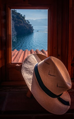 Very picturesque view of lake Atitlan framed in a  small timber window of a cafe /restaurant on the shore of the lake, with a traditional Panama hat on the sill.