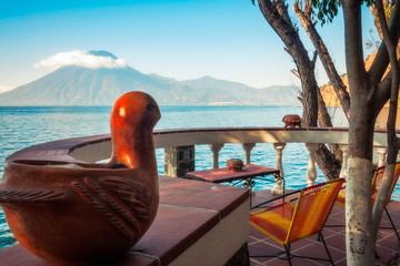 'Bird' View of  Volcano San Pedro with a crown of clouds from a charming round terrace at a resort up hill of the shore of Lake Atitlan in Guatemala.