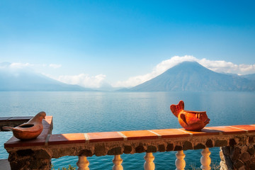 Hazy view of the blue waters of Lake Atitlan in the morning from a sunny terrace with some interesting ceramic decorations. In the background we can see the volcanoes San Pedro and Toliman.