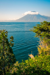 Astounding View of Volcano San Pedro with a crown of clouds  from above at Lake Atitlan in Guatemala, with a timber deck pier and some trees in the foreground.