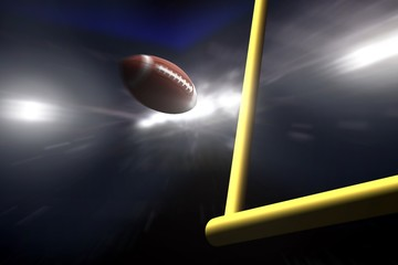 American football over goal post at night