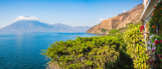 Scenic Panoramic View of Lake Atitlan and Volcano San Pedro in Guatemala from a secluded resort with luxuriant tropical vegetation.