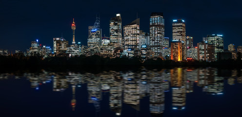 Mesmerizing Waterfront Skyline of Sydney's Central Business District with major modern skyscraper landmarks of Sydney and the City Tower at blue hour with reflections in the bay