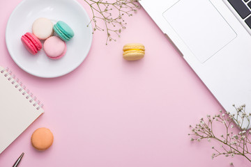 Flatlay of laptop, cake macaron and cup of tea on pink table. Beautiful breakfast with macaroon.