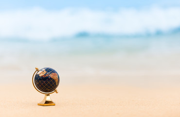Spoed Fotobehang Wereldkaart World travel concept. Globe on the beach.