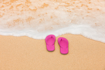 Pair of slippers on white sand beach.