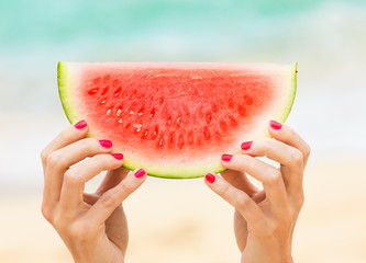 Woman's hand holding slice of watermelon on beach background.