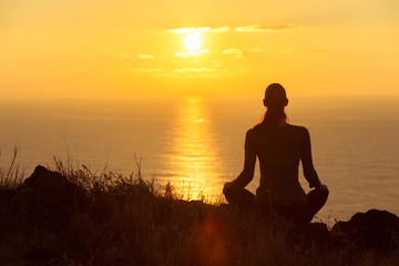 Young woman watching the beautiful sunrise. Peace and relaxation concept.