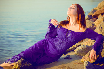Gorgeous sexy young lady at evening sunlights around rocks and water. Woman wearing in purple long dress. Portrait in vintage style. Sweet woman rest on the sea
