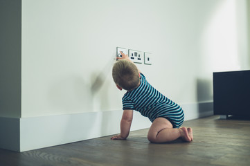 LIttle baby reaching for a plug socket