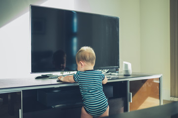 Baby cruising on furniture by TV