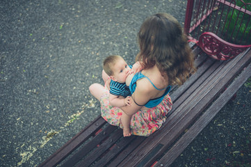 Mother breastfeeding baby on park bench