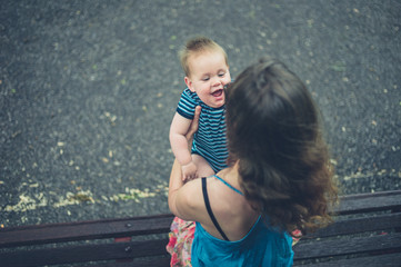 Mother with laughing baby on park bench