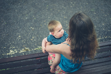 Mother with baby on park bench