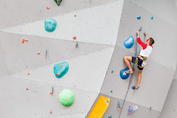 Sportsman or amateur starts to climbing big artificial wall at modern colorful indoor boulder gym