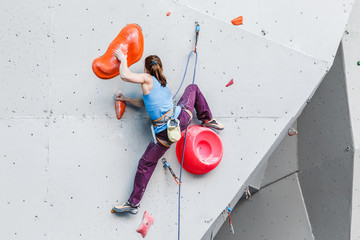 active young and fit woman on artificial climbing rock wall in extreme sport center