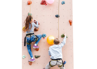 Two sporty kids challenging and climbing artificial boulder on practical wall in gym