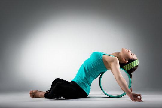 elegant female gym player lying on pilates ring