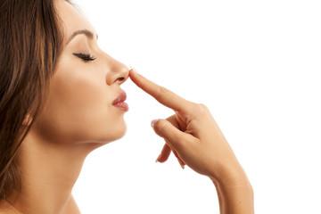 Beautiful young woman touching her nose