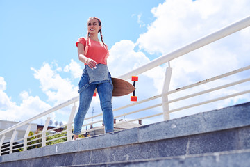 Good-looking female walking with skateboard in hands