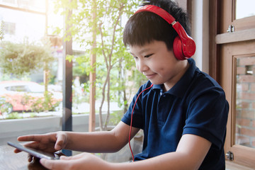 Asian boy sitting and playing tablet computer with headset in the room.