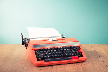 Retro old typewriter with paper on wooden table front mint green background. Vintage style filtered photo