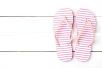 Pink flip flops on white wooden background
