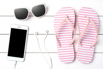 Pink flip flops with summer accessories on white wooden background