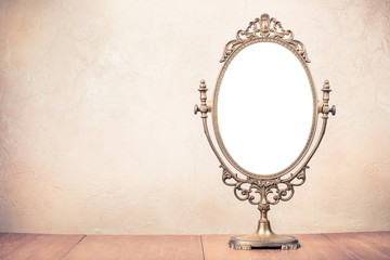 Old vintage bronze makeup mirror frame on table. Retro style filtered photo