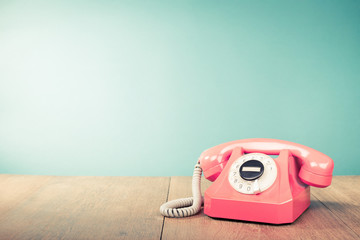 Retro pink telephone front mint green wall background. Old style filtered photo