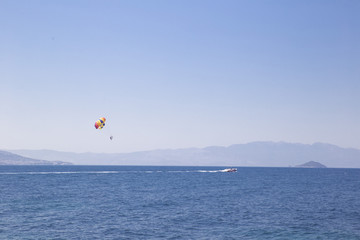 A man flies on a paraglider over the sea, following a boat that rushes along the water against a blue sky and mountains