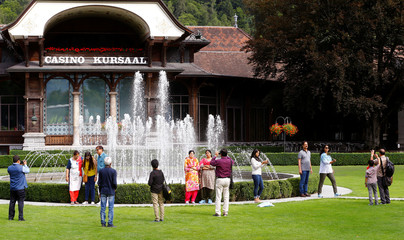 Tourists take pictures at a spa garden in Interlaken