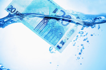 Money concept showing Euro banknote sinking in water as a symbol of global economic crisis