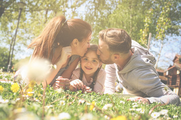 Parent kissing their daughter. Family lying on green grass in meadow.