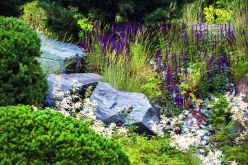 Stones for the alpine slide, house garden landscaping design. Plants and rocks in landscape background