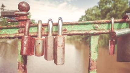 Retro stylized picture of old rusty padlocks on a bridge, love symbol, shallow depth of field.