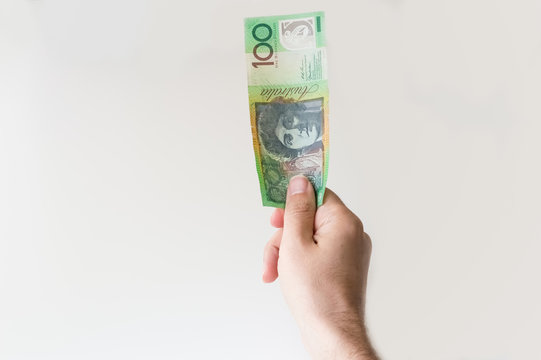Man holding one hundred Australian Dollar note in his hand