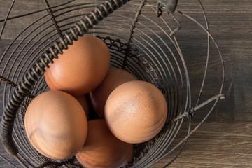 Brown eggs in a vintage metal basket on a brown table