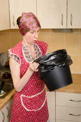 A woman, with a scarf on the head and a red apron, is surprised looking inside a black trash can with a garbage bag, in the kitchen. She is very disturbed by the bad smell