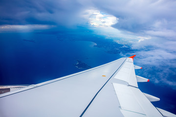 Wing of airplane, clouds and blue sky, view from the window of airplane.