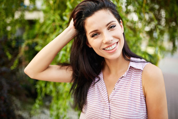 portrait of a smiling woman on a background of green plant