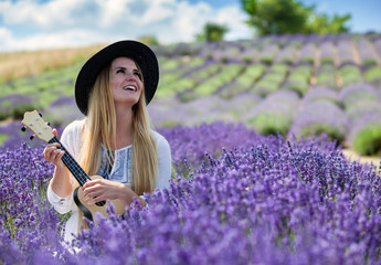 Boho girl playing ukulele in lavender field at summer day, hippie fashion style