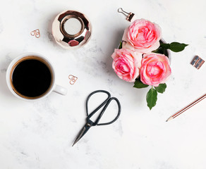 Coffee, flowers and other small accessories on the white marble background