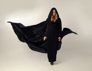 full length portrait of a blonde lady wearing black lace now and hooded cloak, standing pose isolated against creamy background.