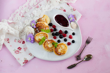 Cottage cheese pancakes on a white plate, garnished with berries and flowers