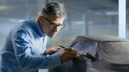 Professional Automotive Designer with Rake Sculpts Futuristic  Car Model from Plasticine Clay. He Works in a Special Studio Located In a Large Car Factory. Wall mural